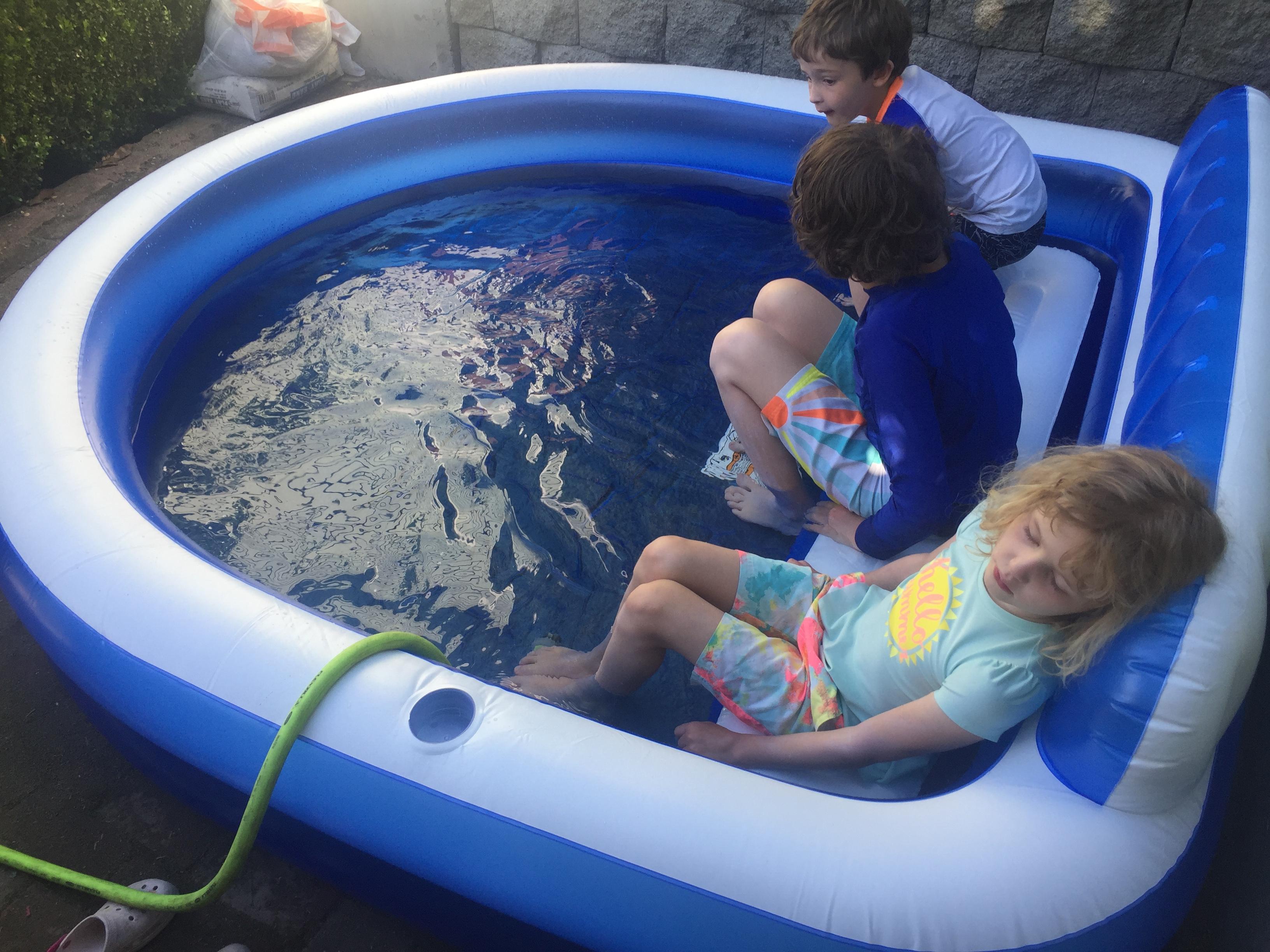 Three kids in one and half foot deep splash pool