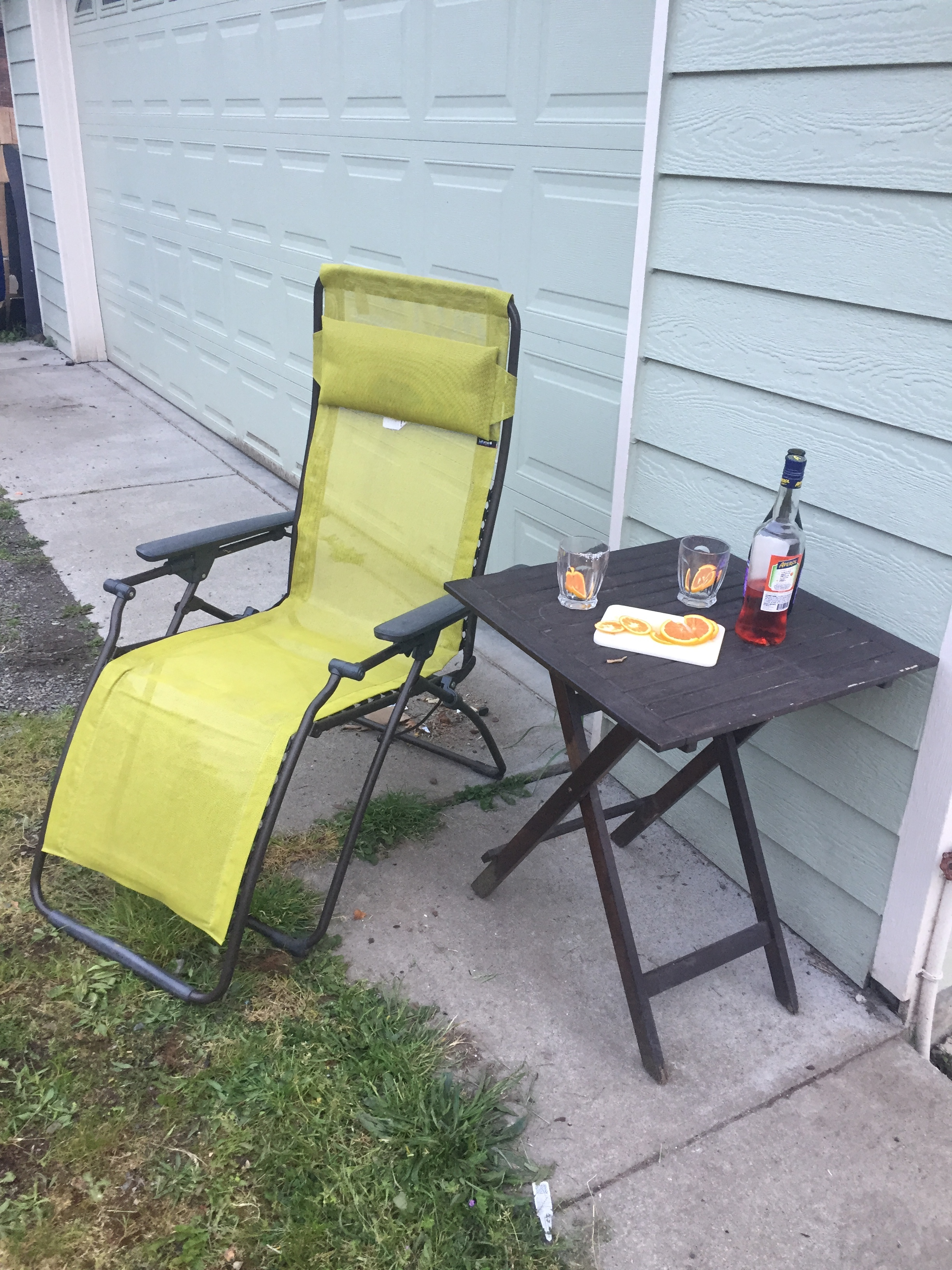 Lafuma reclining lounge chair in lime green next to small table with drink mix
