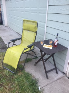 Lafuma reclining lounge chair in lime green next to small table with drink mixings on it