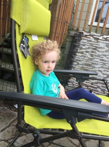 Child sitting in lime green Lafuma lounge chair