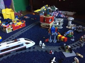 Lego passenger train on tracks going around other Lego creations including buildings and aircraft