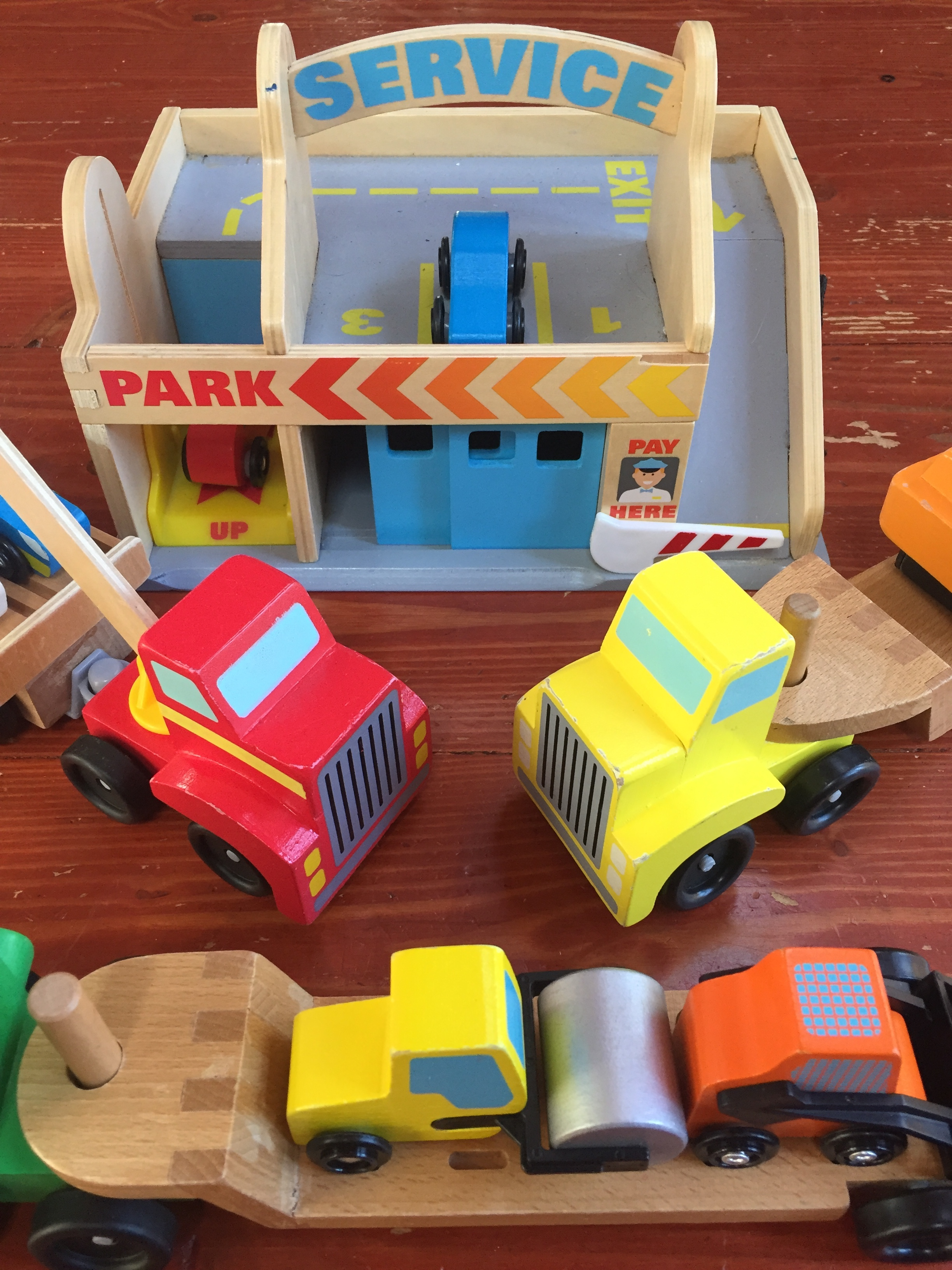 wooden vehicle toys Service Station Garage Play set from Melissa & Doug Skid steer and steam roller on flatbed and other transport trucks