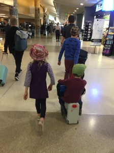 JetKids BedBox being ridden by six year old and pulled by ten year old through airport