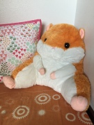 Hamster backrest lumbar support pillow in orange and white on child's bed
