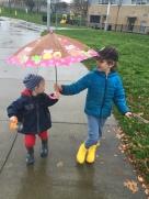 Child holding Stephen Joseph kids' umbrella over toddler younger sibling in rain on sidewalk