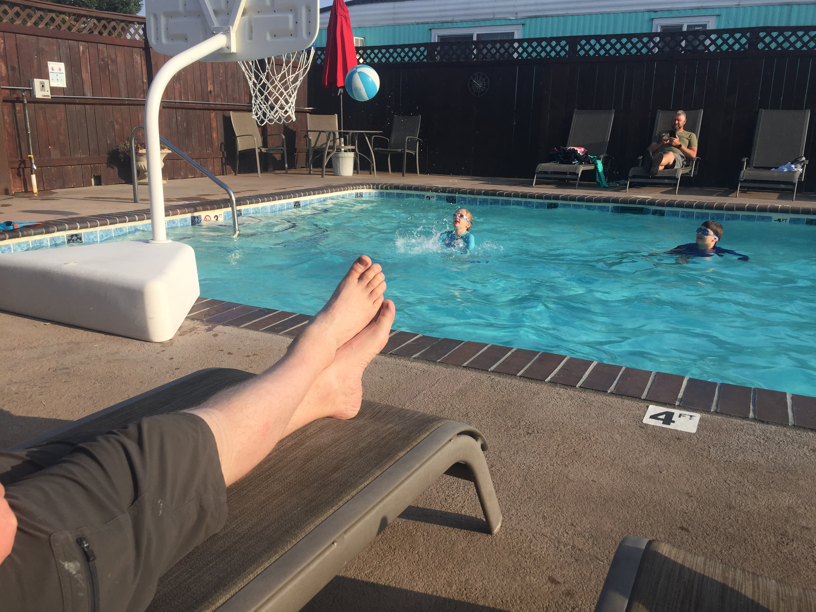 Kids splashing in swimming pool with adult bare feet on lounger poolside in foreground