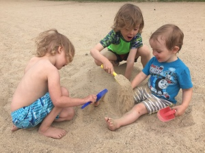 Three kids digging in sand and burying each other in Boise, ID