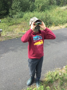Ten year old child using Obuby binoculars on paved trail