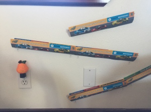 Paper Trax toy car tracks mounted on wall under window