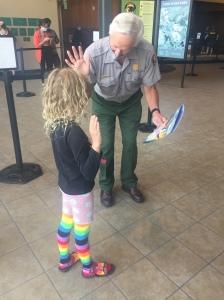 Nine year old girl getting sworn in as Junior Ranger by ranger at