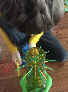 Kerplunk sloth version kids game child placing sticks in clear cylinder tree