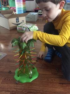 Child playing Kerplunk sloth version sticks and marbles game for kids