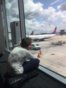 Child sitting on floor next to window at airplane watching airplanes